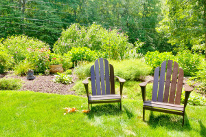 photo of two adirondack chairs in a backyard