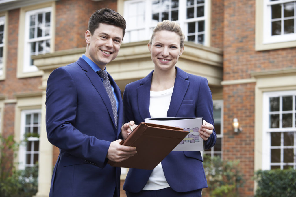 photo of Male And Female Realtor Standing Outside Residential Property